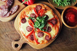 Hot homemade pizza with Pepperoni, paprica, rucola on wooden table. Top view