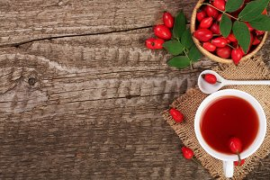 tea with rose hips on old wooden background with copy space for your text. Top view