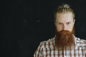 Closeup portrait of young hipster man looking at camera on black background