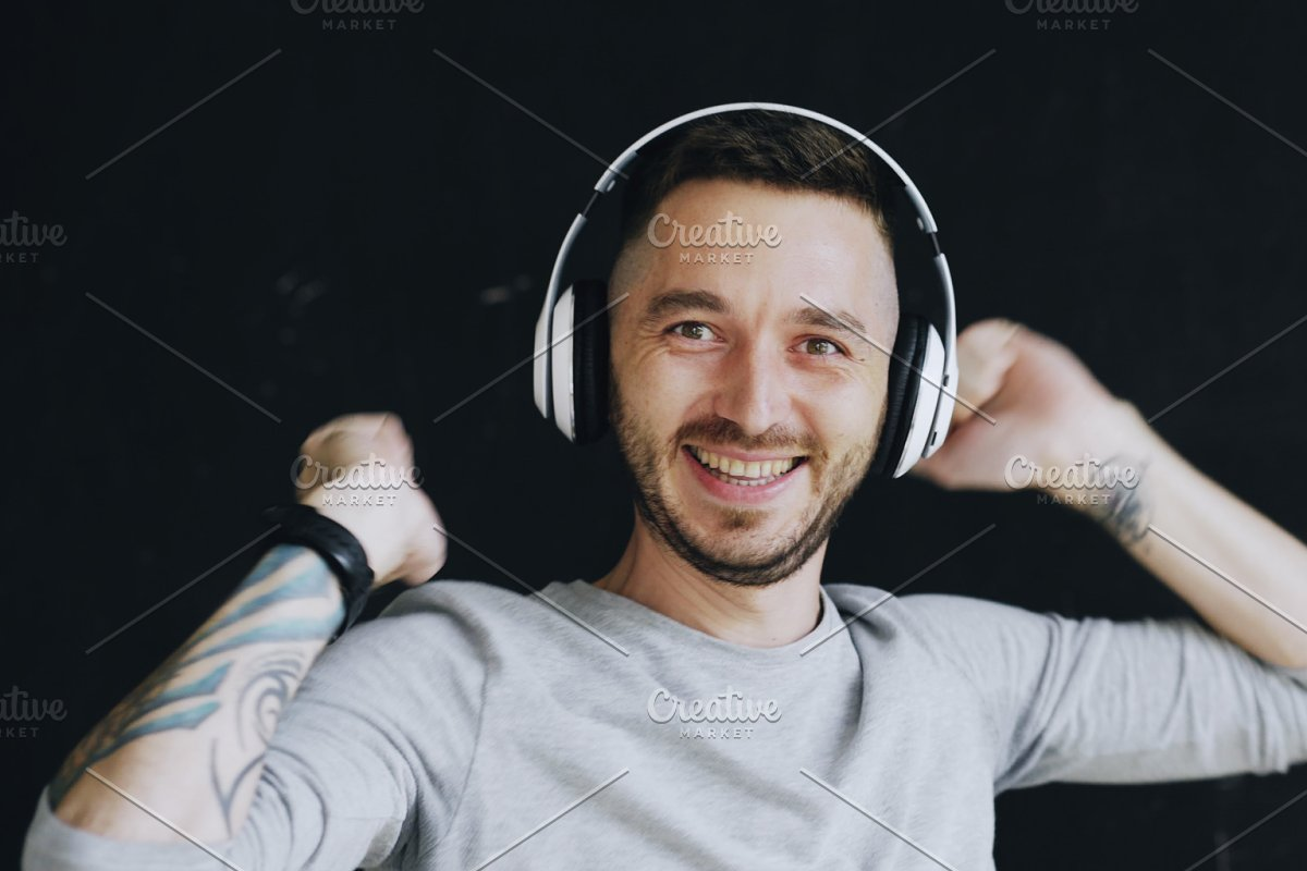 Closeup Portrait Of Young Funny Man Puts On Headphones And Crazy Dancing While Listen To Music On Black Background