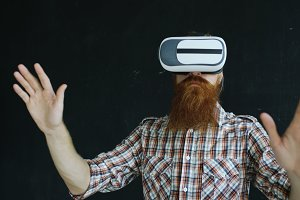 Bearded man wearing virtual reality headset and having 360 VR experience on black background
