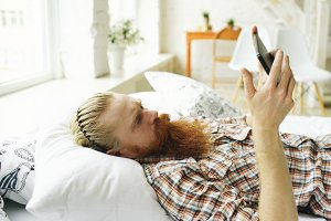 Young bearded man using tablet computer lying on bed in bedroom at home