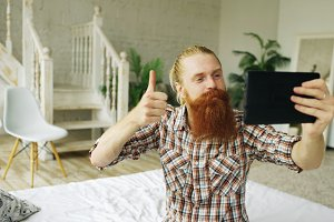 Young bearded man using tablet computer having video chat sitting in bed at home
