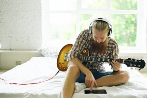 Attractive bearded man sitting on bed learning to play guitar using tablet computer in modern bedroom at home