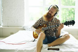 Attractive bearded man in headphones sitting on bed learning to play guitar using tablet computer in modern bedroom