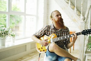 Attractive bearded man sitting on chair learning to play guitar in modern bedroom at home