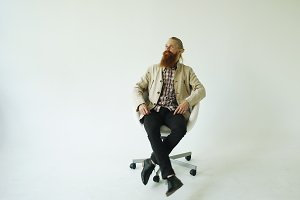 Smiling bearded man turning on swivel office chair on white background