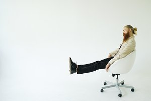 Boring bearded man turning on swivel office chair on white background