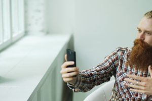 Bearded young hipster businessman talking video chat on smartphone while sitting in offce chair
