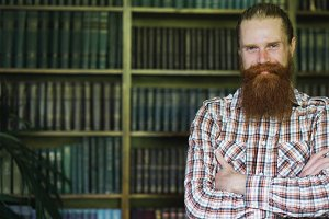 Portrait of young bearded man smiling happy in library and looking into camera