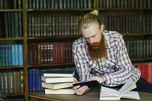 Young bearded student in library reading a book and using tablet computer to prepare for exams