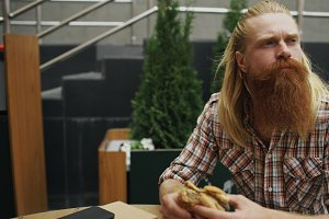 Bearded student man eating burger in street cafe outdoors