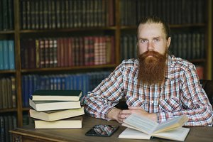 Portrait young bearded man in library and looking into camera