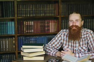Portrait young bearded man smiling happy in library and looking into camera