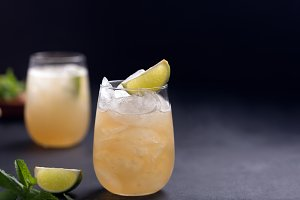 Fresh cocktail prepared with ginger beer, lime and ice. Black background