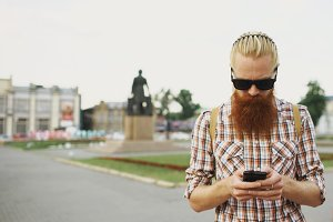 Bearded tourist man with backpack walking street and using smartphone for view map outdoors