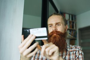 Bearded man online shopping and banking with credit card using smartphone at home