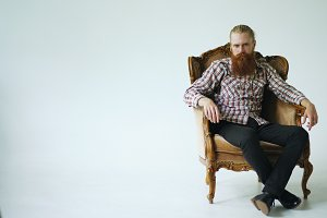 Bearded man sitting luxury armchair and looking into camera on white background