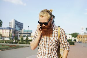 Bearded smiling man with backpack walking street and talking phone outdoors
