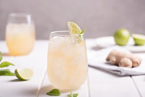 Fresh cocktail prepared with ginger beer, lime and ice. White table