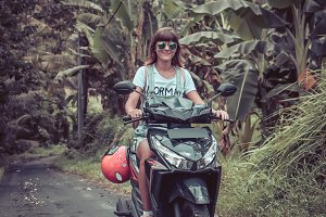 Young happy woman on a motorbike in the jungle rainforest of a tropical Bali island, Indonesia. Freedom concept. Lady on a scooter.