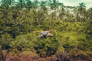 Young tourist woman swinging on the cliff in the jungle rainforest of a tropical Bali island, Indonesia.