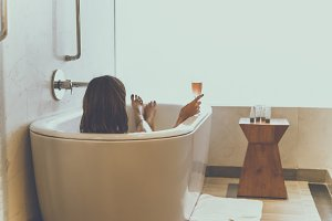 Young attractive woman with champagne glass relaxing in bath. Sexy woman in the bathroom. Female spa.