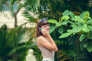 Happy attractive young woman using mobile phone in summer resort on a tropical Bali island, Indonesia.
