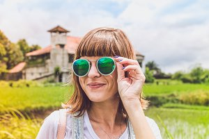 Outdoor fashion portrait of young beautiful lady in sunglasses, summer concept. Rice field on a background. Tropical island of Bali, Indonesia.