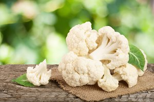 Piece of cauliflower on wooden table with blurred garden background