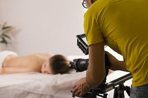 Behind the scenes of medicine video film shooting - nude young woman lying on massage table