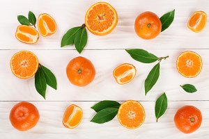 orange or tangerine with leaves on white wooden background. Flat lay, top view. Fruit composition