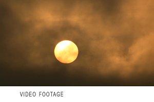 Sun rising, dark clouds flying