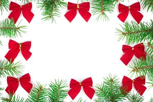 Christmas Frame of Fir tree branch with red bow isolated on white background with copy space for your text. Top view