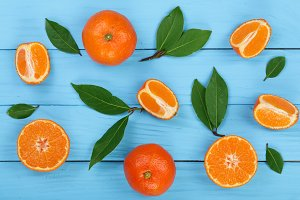 orange or tangerine with leaves on blue wooden background. Flat lay, top view. Fruit composition
