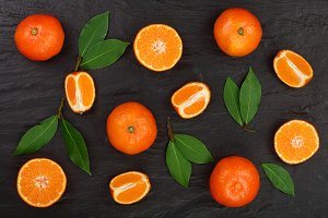 orange or tangerine with leaves on black stone background. Flat lay, top view. Fruit composition