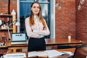 Confident female business owner standing at her work desk folding arms looking at camera in creative design studio