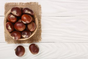chestnut in bowl on white wooden background with copy space for your text. Top view. Flat lay