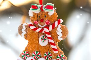 Christmas greeting card with gingerbread man cookie toy hanging on a tree branch