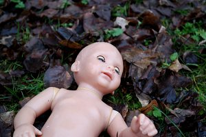 abandoned baby doll in the grassr on the road