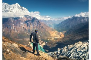 Standing sporty man with backpack on the mountain peak