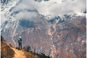 Young woman with backpack on the mountain peak