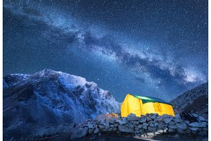 Milky Way, yellow glowing tent and mountains