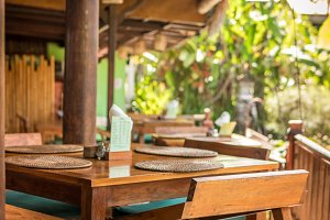 Interior of a tropical restaurant on Bali island, Indonesia. Wooden table and chairs.