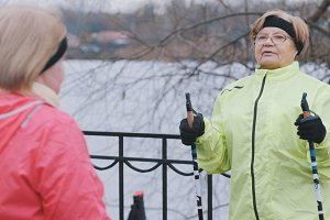Senior woman in green jacket doing warm up exercises outdoor