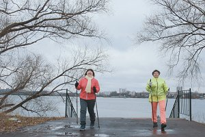 Nordic walking for senior women outdoor - two senior ladies have training outdoor