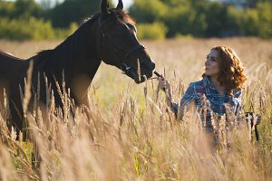 Young woman and horse in the meadow at summer evening