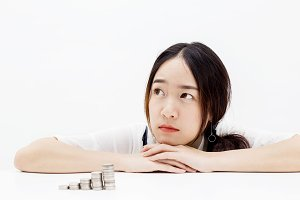 Asian woman thinking while there are coins stacked up in front - investment, finance, money concept