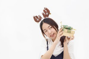 Asian woman wearing reindeer hairband and holding a gift present in white isolated background