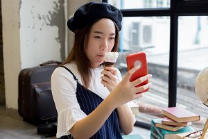 Asian attractive and stylish girl eating ice cream and taking a selfie photo shot